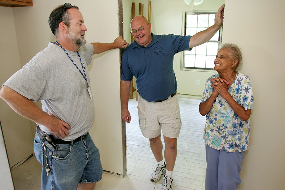 Ken Ward (left) and Dale Kimball visit with Leona Cousins, 95, at her home in Slidell, La., which is being repaired by United Methodist volunteers in this 2006 file photo. The United Methodist Slidell (La.) Disaster Recovery Station has helped rebuild thousands of homes damaged by Hurricane Katrina. Reborn as the Epworth Project at Northshore Disaster Recovery Inc., the project continues to host teams today. File photo by Mike DuBose, UMNS.