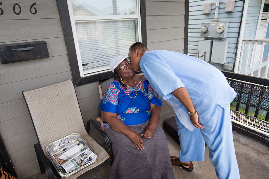 """The Rev. Hadley Edwards kisses Estelle Julian during a visit to her home in New Orleans' 7th Ward. Edwards was going door to door to tell people about """"The Spirit Church,"""" a new United Methodist ministry he is starting there. Edwards says Julian will be his """"first church member."""" Photo by Mike DuBose, UMNS."""