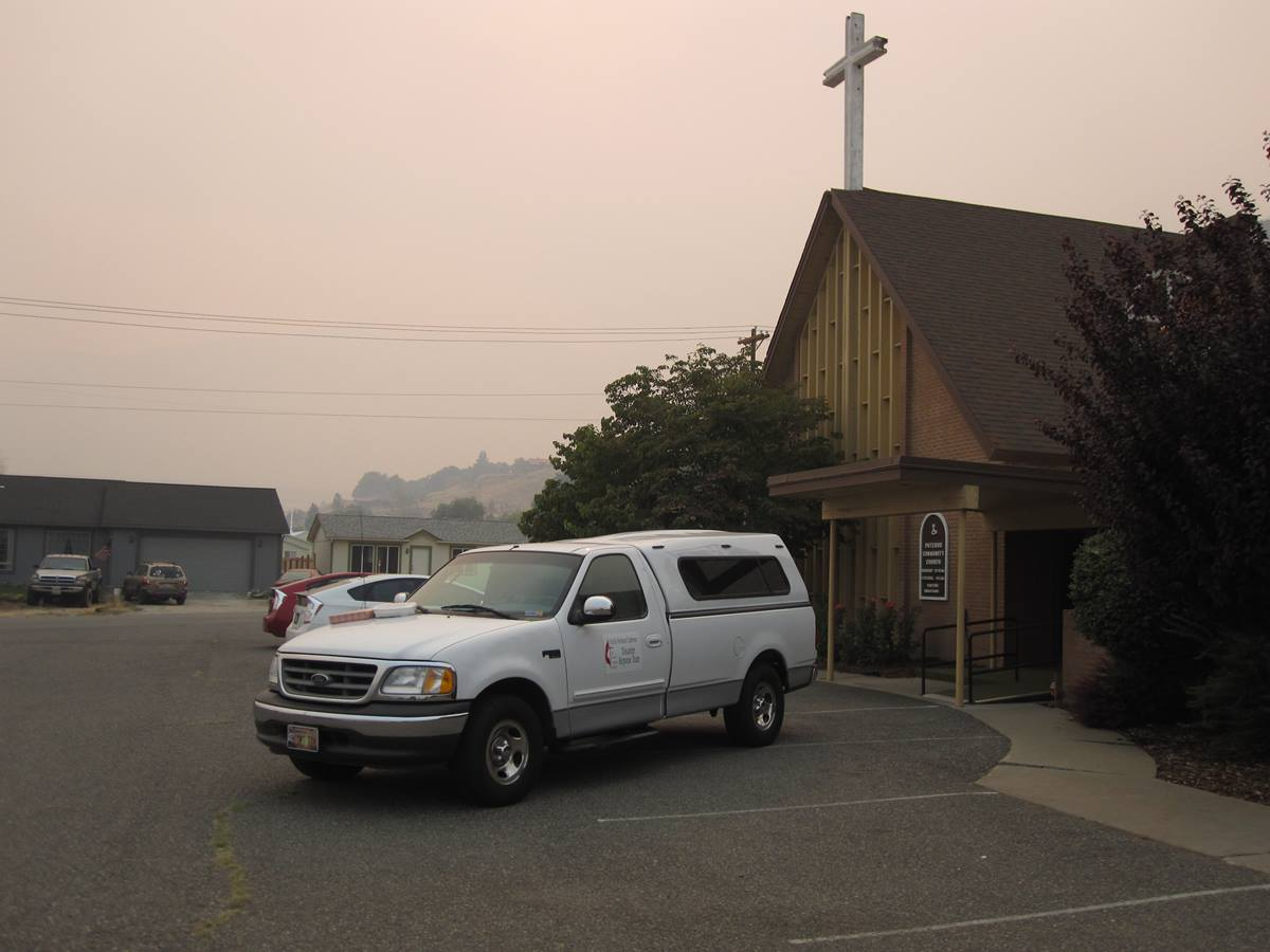 Smoke is evident  from the parking lot of Pateros Community United Methodist Church in Washington, which is serving as a shelter while wildfires rage in the area. The church itself was scorched and the parsonage burned to the ground by a wildfire a year ago. Photo by Jim Truitt