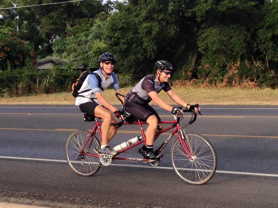 The Rev. Paul Escamilla, pastor of Saint John's United Methodist Church in Austin, Texas, rides in back while church member Toby Sudduth captains a tandem bike on Friday, Sept. 4 near Bastrop, Texas. Church members are joining Escamilla, who recently fractured his clavicle, in working toward riding 670 miles for the church's 67th anniversary and in turn raising funds for mission.
