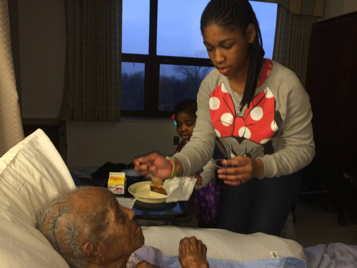 Erica, 14, feeds Mildred Tharpe, 101, the oldest member of Resurrection United Methodist Church in Chicago, during a recent visit. The Rev. Julie Fleurinor said she often takes the children with her on nursing home visits because the residents don't often get to see young children, and they enjoy visiting with them.