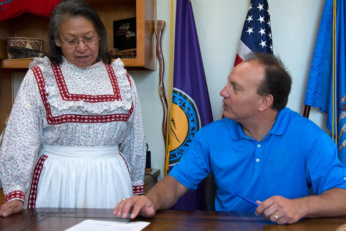 """Chief Gary Batton of the Choctaw Nation signs a proclamation declaring the second Monday of October as """"Indigenous Peoples' Day."""" Witnessing the signing is the Rev. Billie Nowabbi, a retired pastor in the Oklahoma Indian Missionary Conference. Photo courtesy of the Choctaw Nation of Oklahoma."""