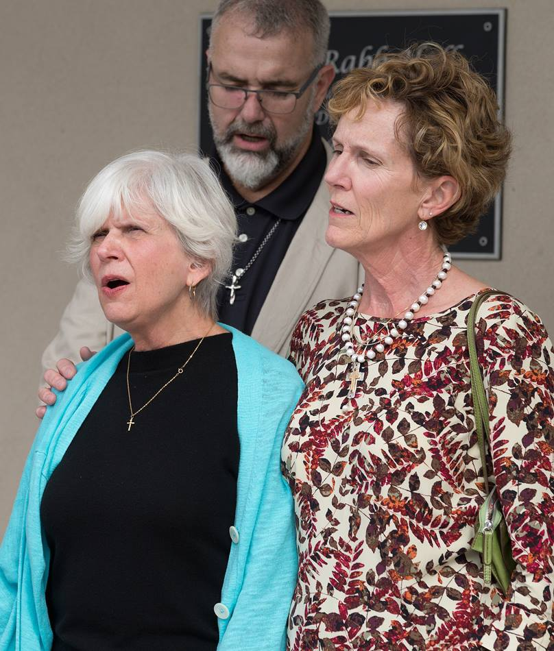 Suzanne Rabb (left) and Cindy Dixon (right) sing a hymn during the dedication of Dixon Rabb Hall at the Sager Brown Depot in Baldwin, La. At rear is the Rev. Tom Hazelwood, former head of U.S. disaster response for UMCOR. Photo by Mike DuBose, United Methodist Communications.