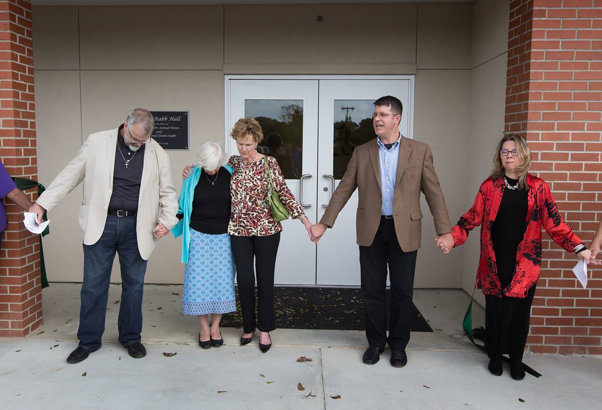The Rev. John Cannon (second from right) leads the closing prayer during the dedication of Dixon Rabb Hall at the Sager Brown Depot in Baldwin, La. From left are: the Rev. Tom Hazelwood, former head of U.S. disaster response for UMCOR; Suzanne Rabb; Cindy Dixon; Cannon, superintendent of the church's Acadiana District; and the Rev. Denise Honeycutt, head of UMCOR. Photo by Mike DuBose, United Methodist Communications.