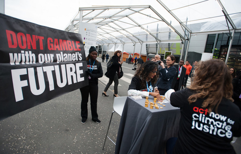 Climate justice activists organized by ACT Alliance stage a protest stunt during the U.N. climate summit in Paris, France. Photo by Ryan Rodrick Beiler/LWF, courtesy of World Council of Churches