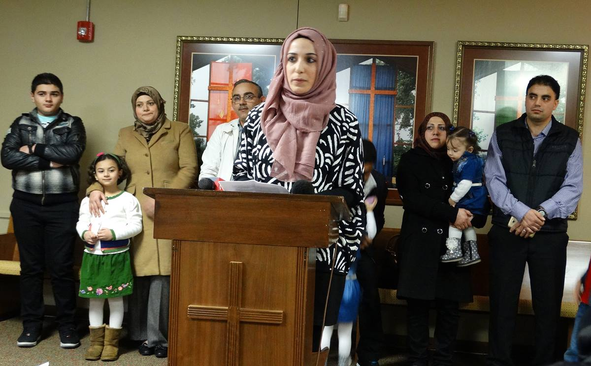 With three Syrian refugee families standing behind her, Nora Basha, with the Syrian American Council of Indiana, speaks during a press conference before a Dec. 11 rally and candlelight vigil in support of Syrian refugee families. The event was held by the council at Epworth United Methodist Church in Indianapolis. Photo by Dan Gangler, UMNS