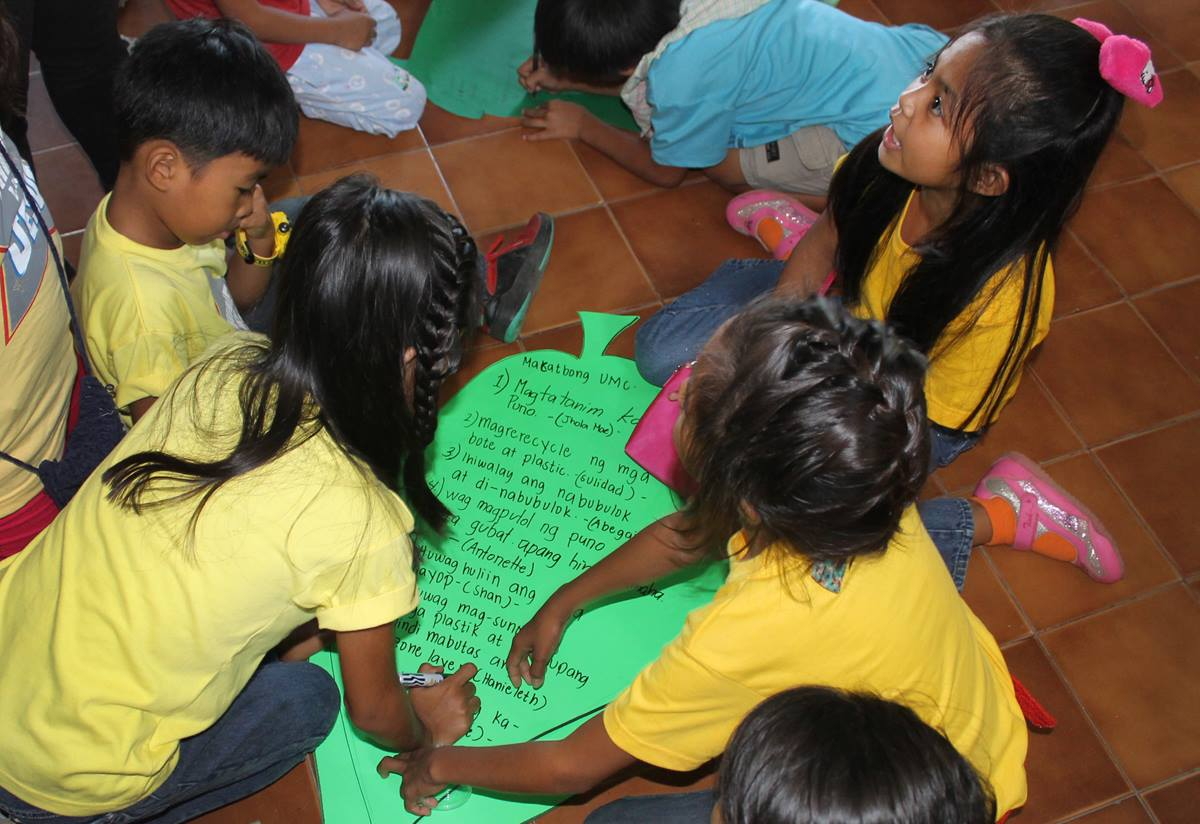 Filipino children ages 5 to 12 write ways they can help reduce the Earth's temperature. Examples (written on green paper leaves) include avoiding smoking, planting more trees, conserving water and electricity, recycling plastic and paper.