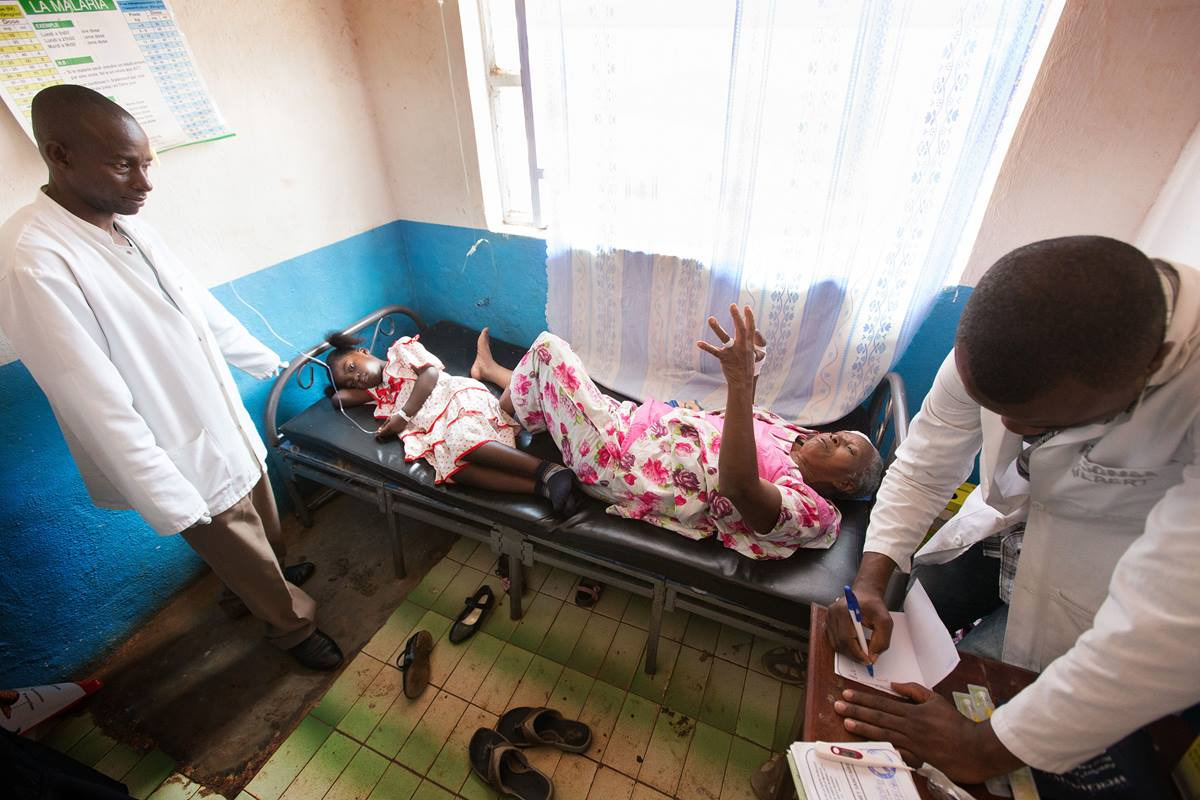 Gael Nonge (left, on bed) shares a hospital bed with Margelitte Enanga at The United Methodist Church's Irambo Health Center in Bukavu, Democratic Republic of Congo. The two patients are not related. There were not enough beds for each to have her own.