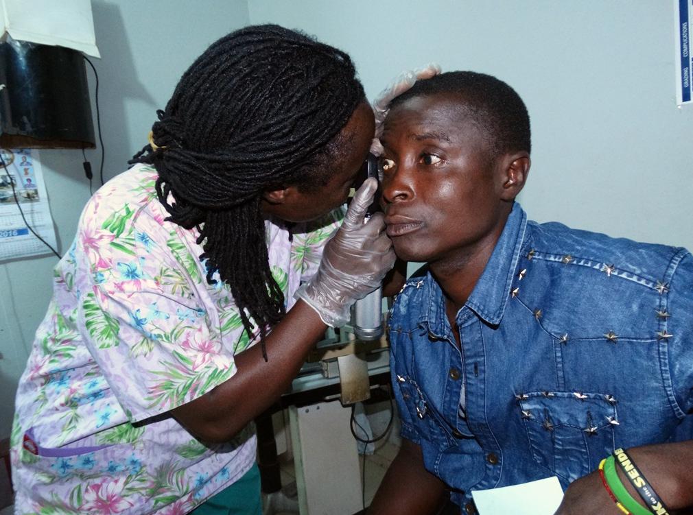 Cataract surgeon Isatu Sesay examines Mohamed Kamara's eyes at the Lowell and Ruth Gess United Methodist Eye Hospital in eastern Freetown. Kamara is an Ebola survivor receiving free treatment.