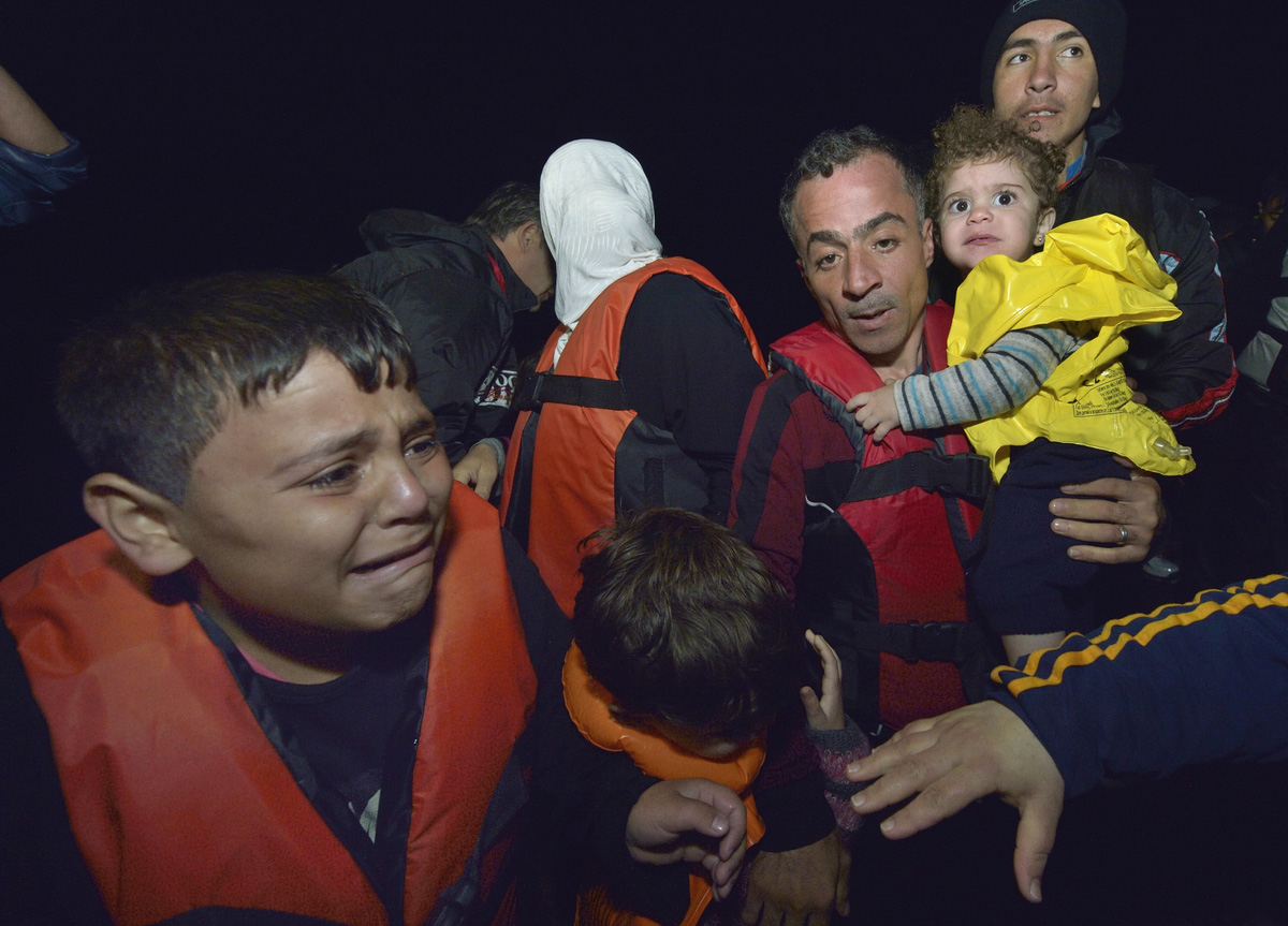 Refugees disembark at night from a private fishing boat that rescued them at sea, bringing them into the harbor at Skala Sikaminia, on the Greek island of Lesbos, on November 1, 2015.  A seven-person United Methodist group traveled to Lesbos in January to help care for such refugees. Photo by Paul Jeffrey.