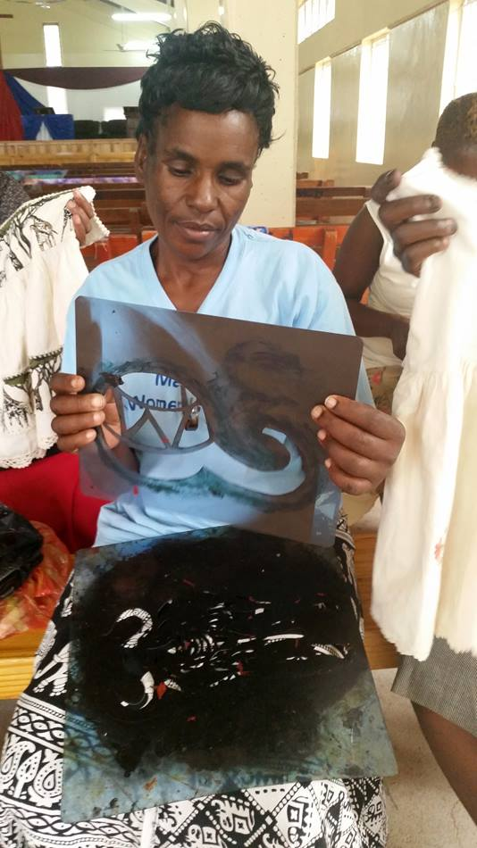 Emilia Mafuratidze holds an X-ray film that she is recycling as a stencil to print fabric during a workshop  in Zimbabwe held by the Chitungwiza-Marondera District women's union March 1-3, 2016. Photo by Eveline Chikwanah, UMNS