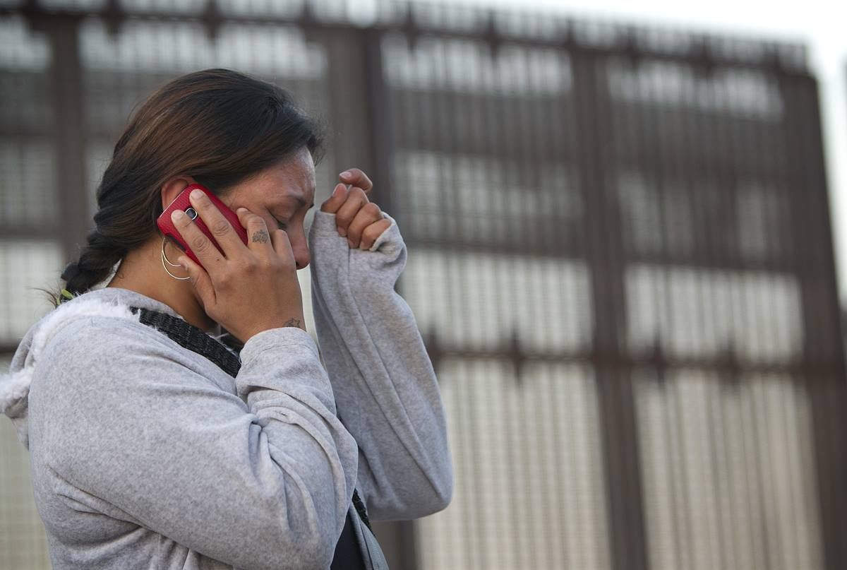 Nancy, who was deported from the U.S. after a traffic violation, cries as she speaks with her mother in Los Angeles from the Mexican side of the massive border fence in Tijuana in December 2012.