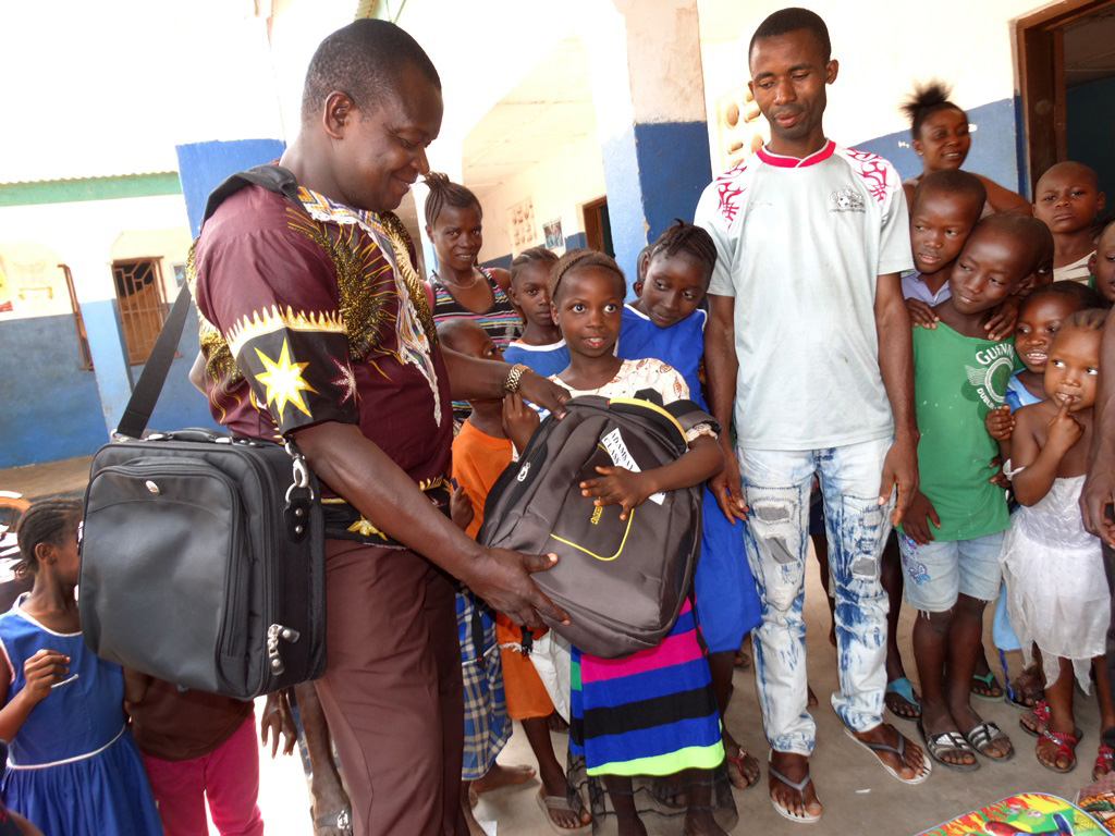 Adamsay Conteh, a student at The United Methodist Church Primary School in Mamaka, Sierra Leone, receives a backpack containing uniforms, books and other materials from Leonard Ben-Gbloa, education secretary for primary schools. Photo by Phileas Jusu, UMNS