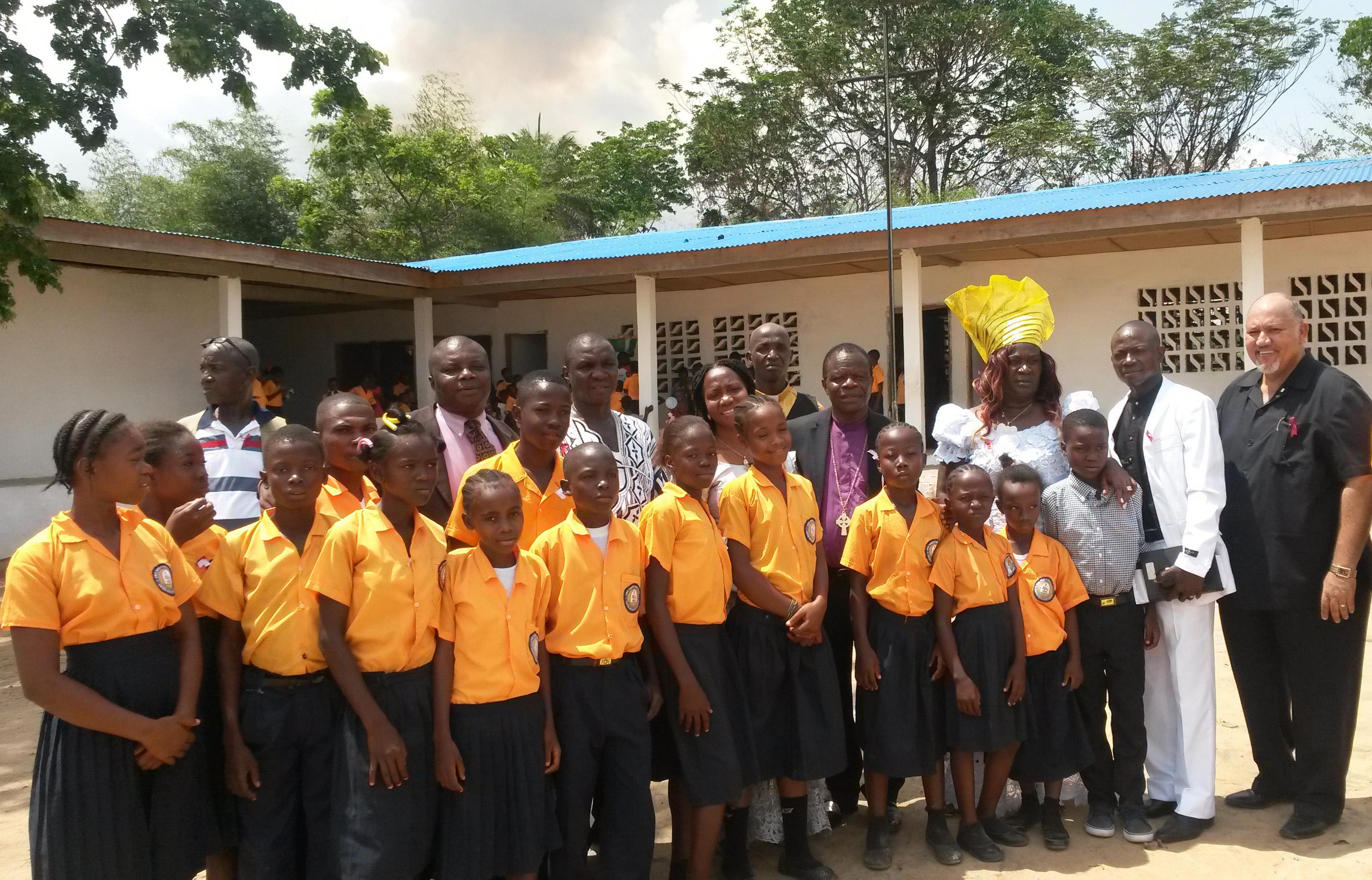 Members of leadership of The United Methodist Church in Liberia stand with students of the Eric Scott Memorial United Methodist School in Bopolu City, Gbarpolu, Liberia.