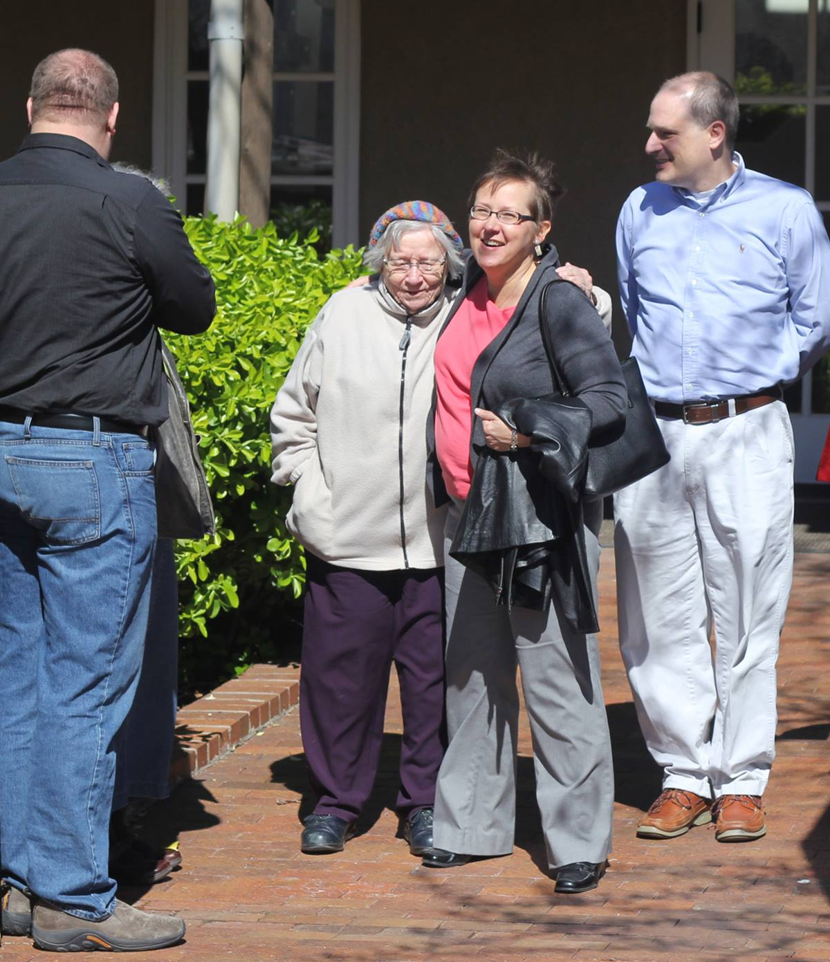 """The Rev. Cynthia Meyer (second from right) gets a hug and well wishes from supporters after a meeting with United Methodist Bishop Scott Jones March 28 in Wichita, Kan. Meyer faces church disciplinary charges after she announced she was in a """"committed relationship"""" with another woman."""