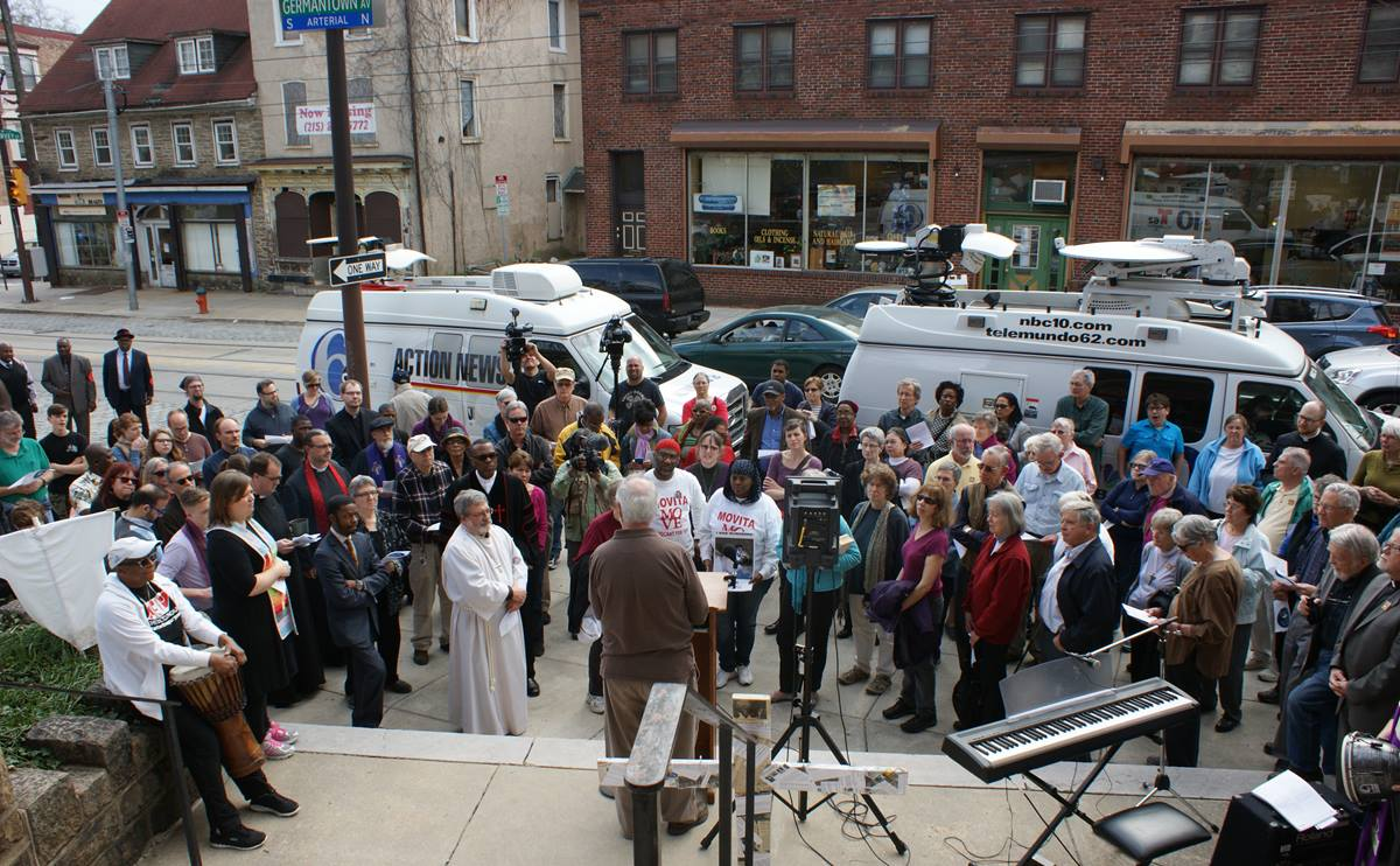 A crowd of more than 200 people of many faiths listens prior to walking through Philadelphia's gun damaged Germantown neighborhood.