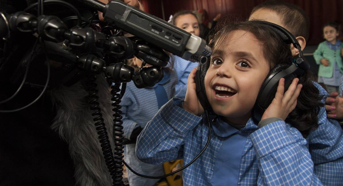 "A Syrian girl at a school in the refugee camp of Bourj el-barajneh in Beirut in 2015 has fun with the ""Beyond Bethlehem"" crew's audio gear. A 2015 file photo courtesy of Dan Bracken"