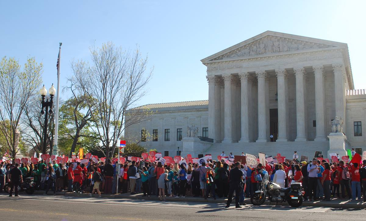 Demonstrators stand outside the U.S. Supreme Court on April 18 as the court hears oral arguments regarding the legality of two Obama Administration policies that would defer deportation for about 5 million immigrants. Photo by Walker Weatherly, Board of Church and Society