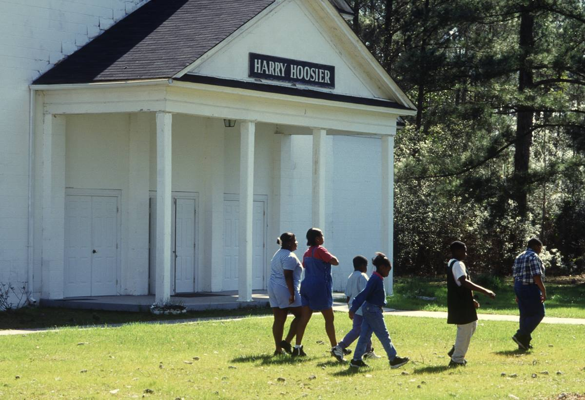 Children walk past Harry Hoosier Hall at Gulfside Assembly in Waveland, Miss., in 1997.