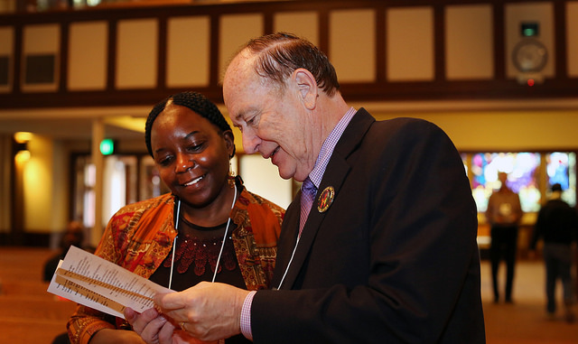 """Dr. Pauline Muchina and the Rev. Donald E. Messer look over the program before the start of  """"AIDS is Not Over!...Global Issues and the Church"""" held at Rose City Park United Methodist Church in Portland, Ore."""