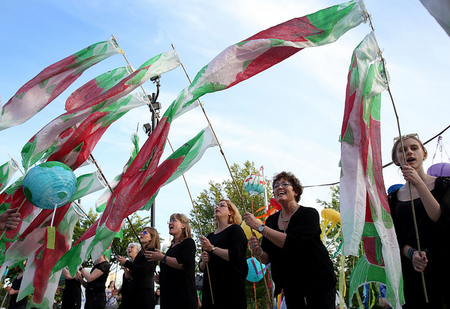 Members of the KEFAS Choir from Denmark wave salmon wind socks during the May 12 General Conference Climate Vigil at Oregon Convention Center Plaza in Portland. Photo by Kathleen Barry, UMNS.