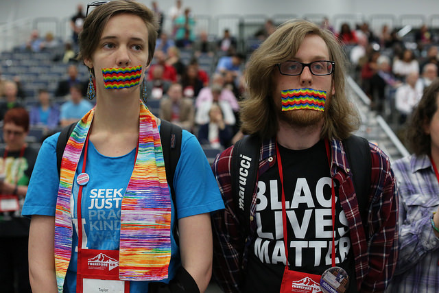 United Methodists in support for LGBTQ community in the church ask for an apology when Dorothee Benz from the New York Conference was called out of order during discussion of Rule 44 at the 2016 United Methodist General Conference in Portland, Ore. Standing with their mouths taped are (from left) Taylor Gould from the Iowa Conference and Sean Crews from the Oklahoma Conference. Photo by Kathleen Barry, UMNS