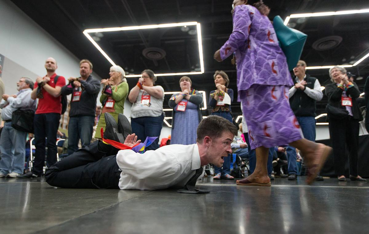 The Rev. Will Green lies on the floor of the 2016 United Methodist General Conference in Portland, Ore., with his hands and feet bound to protest the denomination's policies on human sexuality. Delegates returning from their lunch break passed by protestors on the floor and lining the entry to the meeting area. Photo by Mike DuBose, UMNS