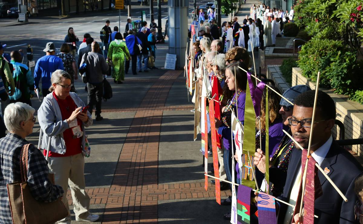Theon Johnson III (at right) and others in support of LGBTQ clergy line the entryway to the 2016 United Methodist General Conference May 18 in Portland, Ore.  The demonstration was carried out in silence as attendees walked past to enter the Oregon Convention Center. Photo by Kathleen Barry, UMNS