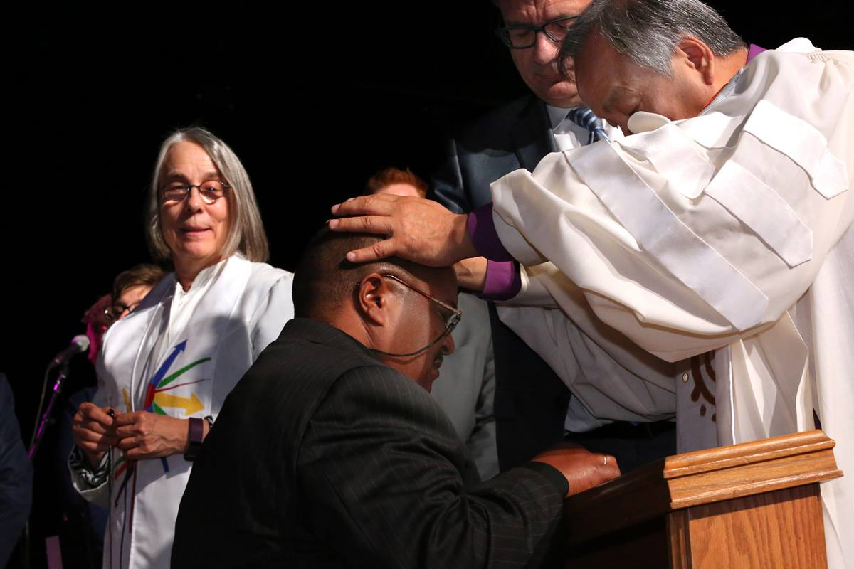 Bishop Hee-Soo Jung commissions Leo Garcia as a missionary May 19 at the 2016 United Methodist General Conference in Portland, Ore. In the background are Catherine Whitlatch and Thomas Kemper from the United Methodist Board of Global Ministries. Photo by Kathleen Barry, UMNS
