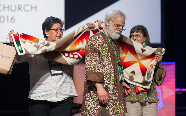 """The Rev. L. Fitzgerald """"Gere"""" Reist II (center) is honored for his years of service as secretary of the United Methodist General Conference during the denominational meeting May 20 in Portland, Ore. Presenting him with a blanket are Cynthia Kent (left) and Raggatha Calentine. Photo by Mike DuBose, UMNS"""
