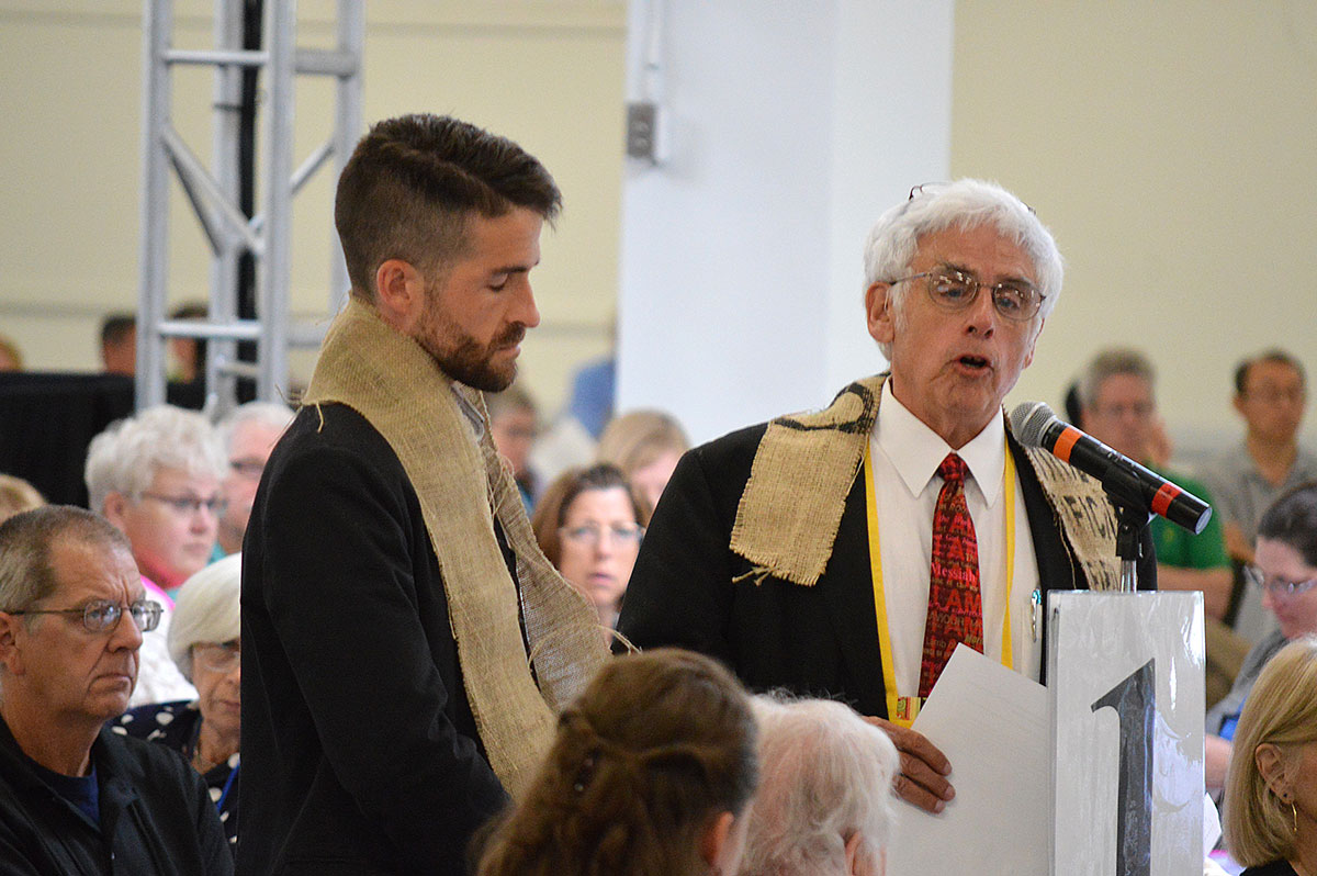 "The Revs. Will Green (left) and John Blackadar offer a resolution that the New England Conference of The United Methodist Church ""will not conform or comply with provisions of the Discipline which discriminate against LGBTQIA persons,"" during the June 2016 conference meeting in Manchester, N.H. Photo by Beth DiCocco, New England Conference."