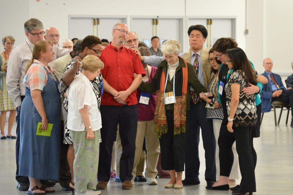 """Church members stand with the Rev. Donald """"Skip"""" Smith, who said he would leave the New England Conference after the non-conformity vote. He later told his district superintendent that he would stay. Photo by Beth DiCocco, New England Conference"""