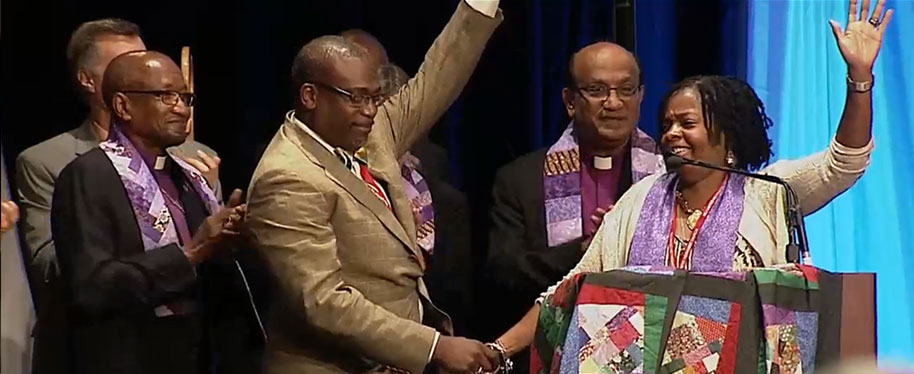 The Rev. Cynthia Moore-Koikoi held the hand of her husband– the Rev. Rafael Koikoi — as she accepted her election as bishop by the Northeastern Jurisdiction. Her bishop, Baltimore-Washington Episcopal Area Bishop Marcus Matthews, left, applauds. Boston Episcopal Area Bishop Sudarshana Devadhar stands behind her. Photo courtesy of Baltimore-Washington Conference.
