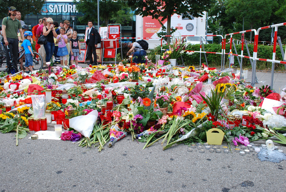 People stop alongside a makeshift memorial to victims of the July 22 Olympia Mall shooting in Munich that killed nine and left 27 injured. Photo © Volker Kiemle
