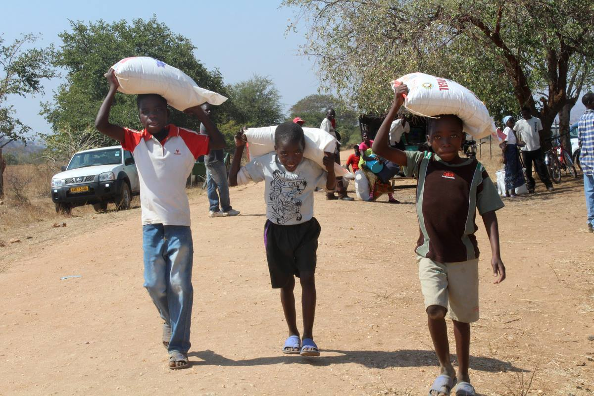 Young boys leave Rutuka United Methodist Church in Rushinga, Zimbabwe, with bags of meal. The denomination organized food distributions to help those in drought-ravaged areas. A UMNS photo by Eunice Kadiki