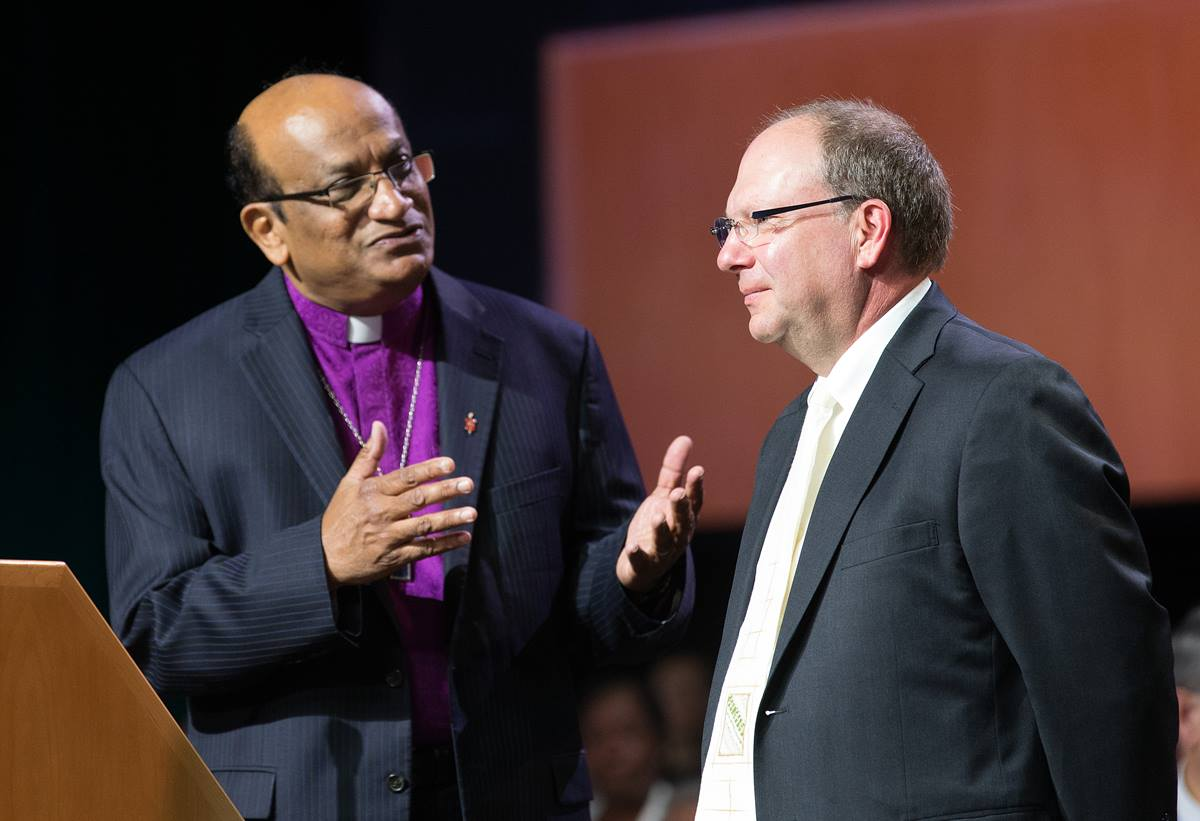 Bishop Sudarshana Devadhar (left) of the Boston Episcopal Area welcomes the Rev. J. Christian Giesler of the Moravian Church (Northern & Southern Provinces) to the 2016 United Methodist General Conference in Portland, Ore. Photo by Mike DuBose, UMNS