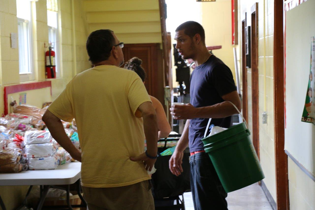 The Rev. Jeff Newton, left, pastor of Trinity United Methodist Church, helps a Kokomo family stock up on food and other supplies after the recent tornado that displaced many in the community. Photo by Skyler Nimmons