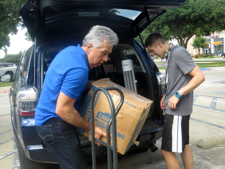 Bishop Ruben Saenz Jr. helps son Isaac unload boxes on Aug. 23 at the University of Texas at Arlington. Photo by Sam Hodges, UMNS