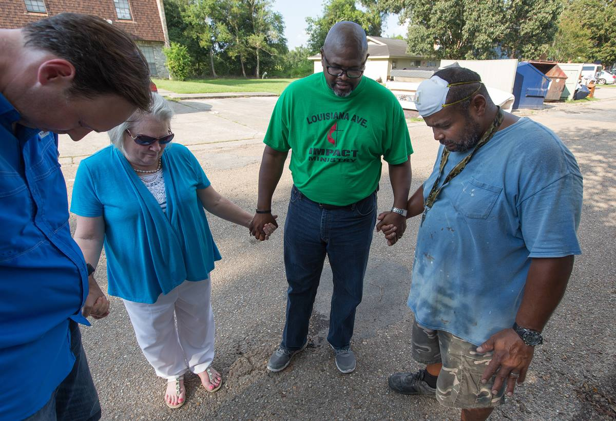 The Rev. Robert Johnson (second from right) leads a prayer with maintenance worker Kevin Oliver (right) at a flood-damaged apartment complex in Duson, La. Praying with him are the Revs. Todd Rossnagel (left) and Susan Ferguson.