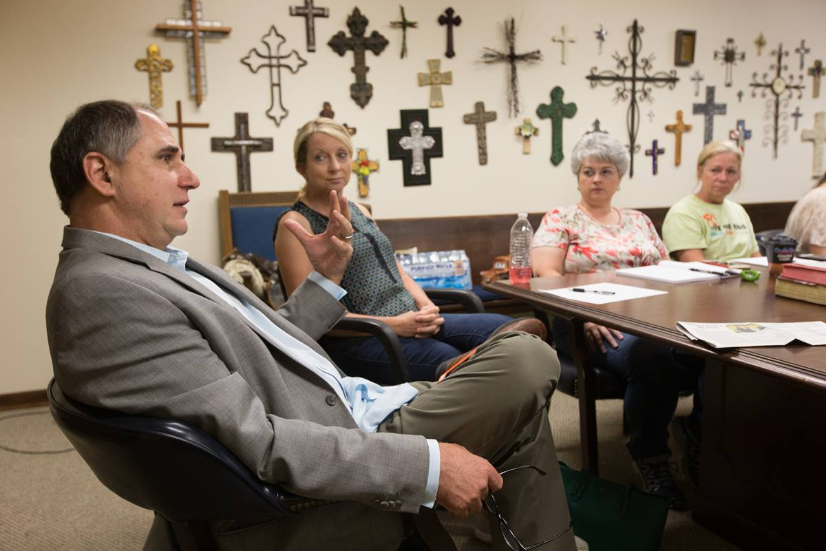 The Rev. Mark Crosby (left) meets with members of the disaster relief group at Live Oak United Methodist Church in Watson, La. The group has been meeting daily during the flooding crisis in southern Louisiana.