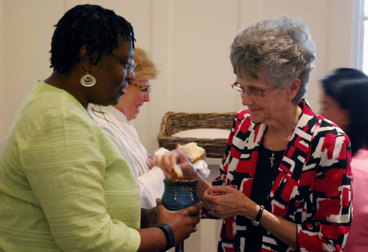 The Rev. Tamara Brown, a director from the Kentucky Conference, serves communion to Philadelphia Area Bishop Peggy Johnson, a fellow director, during the closing worship service of the Sept. 21-24, 2016 meeting of the United Methodist Board of Church and Society.