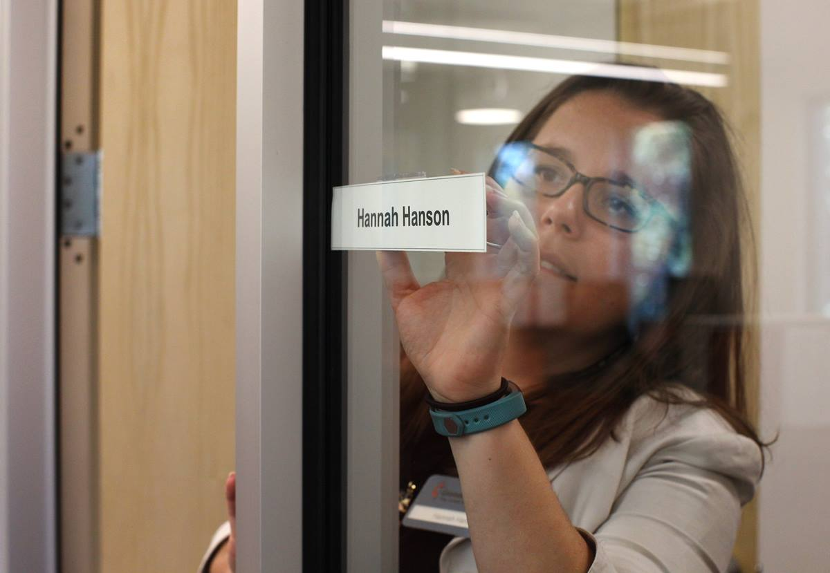 Hannah Hanson, director of young adult mission service, places her name tag on her new office in Atlanta.