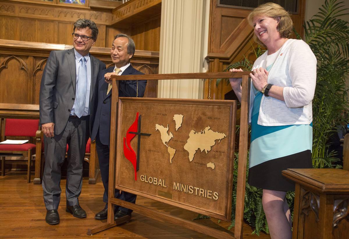 Bishop Sue Haupert-Johnson from the North Georgia Conference presents a wooden map featuring continents and the United Methodist cross and flame to Thomas Kemper and Bishop Hee-Soo Jung following the dedication inside Grace United Methodist Church.