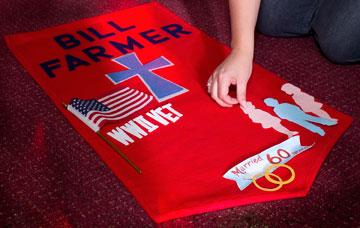 Ann Hill arranges symbols on a banner honoring Bill Farmer.