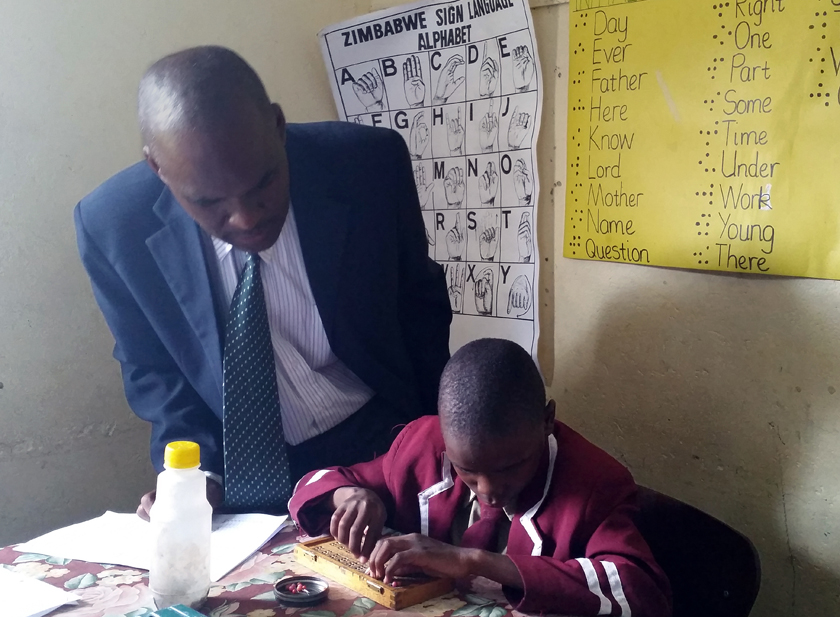Daniel Chiomba assists Kudzai Antonyo, 9, who is learning the basics of Braille. Photo by Eveline Chikwanah, UMNS.