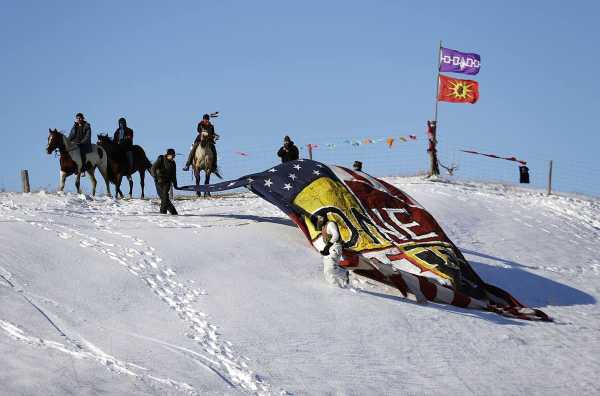 """Veterans unveil a banner that reads """"One Water"""" on a hillside across from the Oceti Sakowin camp where people have gathered to protest the Dakota Access oil pipeline in Cannon Ball, N.D., Sunday, Dec. 4, 2016. Tribal elders have asked the military veterans joining the large Dakota Access pipeline protest encampment not to have confrontations with law enforcement officials, an organizer with Veterans Stand for Standing Rock said Sunday, adding the group is there to help out those who've dug in against the four-state, $3.8 billion project. Photo by David Goldman, AP"""