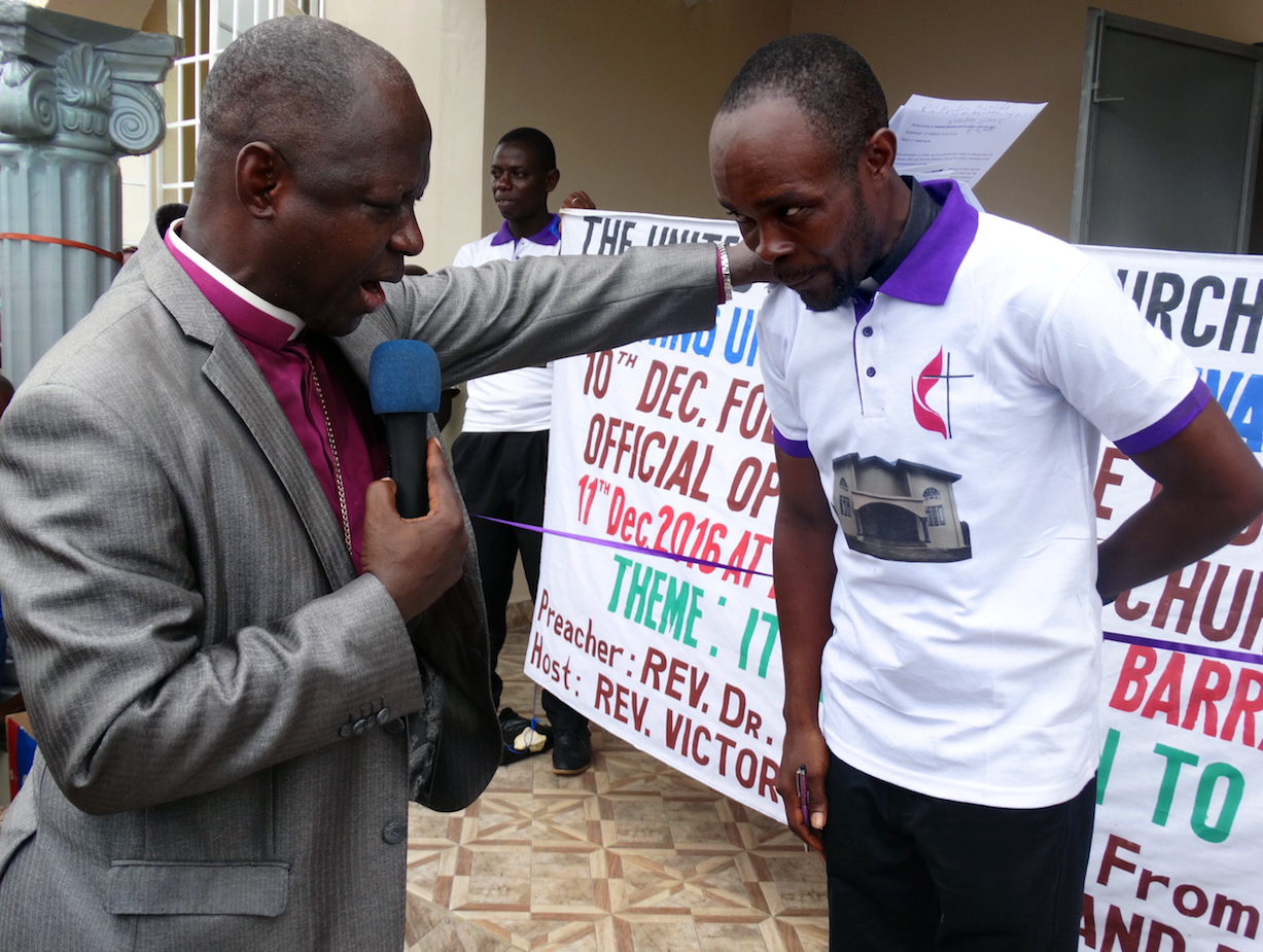 Bishop John Yambasu prays for the Rev. Victor Kainboy for his leadership of the new church in Pujehun. Photo by Phileas Jusu, UMNS.
