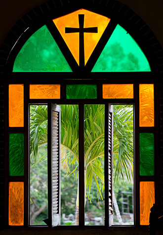 A stained glass window frames a view of palm trees outside the chapel at Camp Canaan, a Methodist retreat center near Santa Clara, Cuba. Photo by Mike DuBose, UMNS.