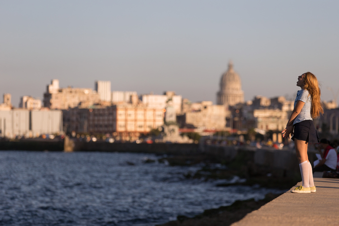 A student stops to sing from atop the Malecón seawall in Havana. Photo by Mike DuBose, UMNS.