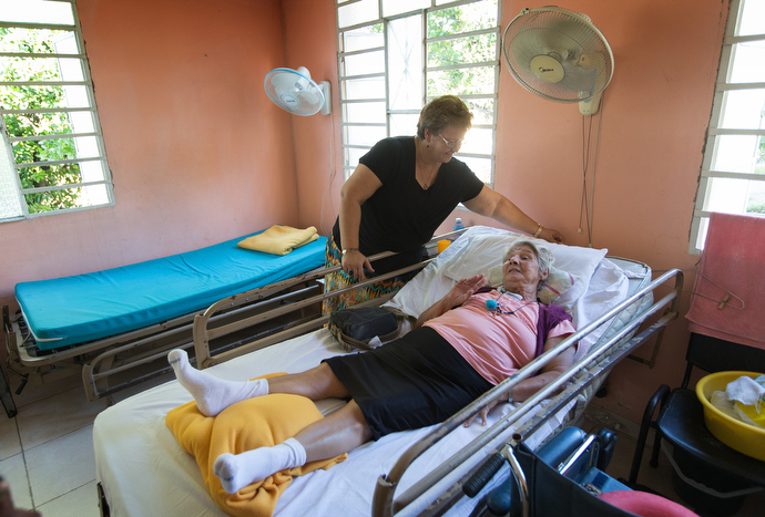 """Susan Reyes, director of the Methodist Christian Home for retired pastors in Havana, visits with resident Delores Pérez. """"Delores is a woman of faith. She has helped us a lot spiritually. She is 83 years old and she is like a girl,"""" Reyes says. Photo by Mike DuBose, UMNS."""